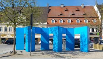 Ins Blaue hinein, 2017, Installation für den Kulturweg der Stadt Pfaffenhofen während der Gartenschau, Holzunterkonstruktion mit Absperrband umwickelt, h: ca. 2,75 cm, b: ca. 2,70 cm, l: ca. 10 m